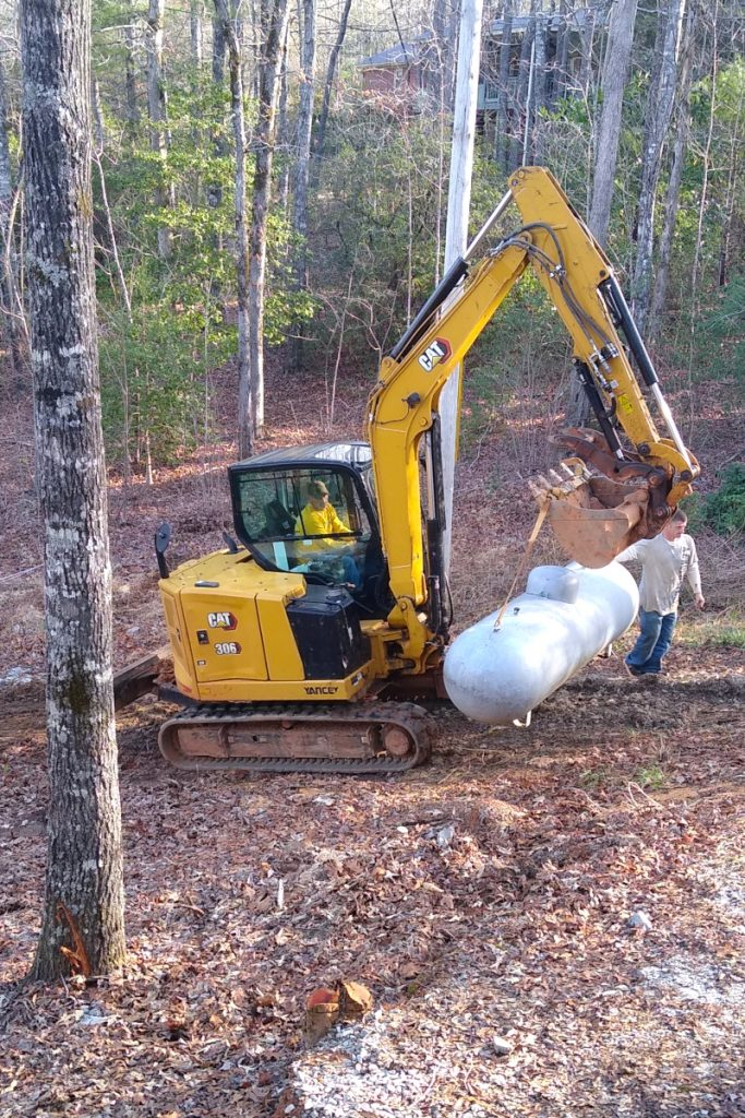 Jerry and Jonathan using the track hoe to move the propane tank.