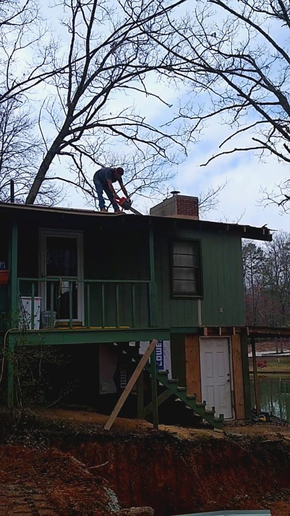 Man cutting roof sheathing with a chainsaw