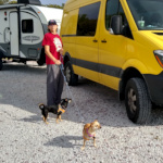 Sue with doggies beside van with RV in tow